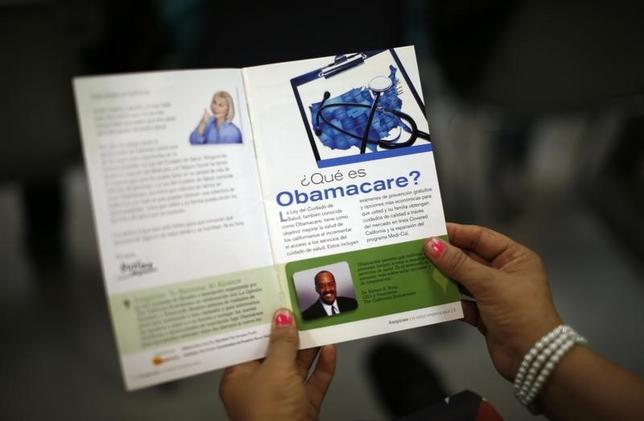 A woman reads a pamphlet in Spanish at a health insurance enrollment event in Cudahy, California March 27, 2014.  REUTERS/Lucy Nicholson