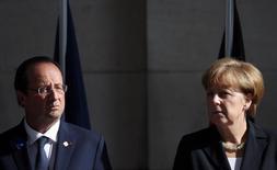 Канцлер Германии Ангела Меркель и президент Франции Франсуа Олланд на церемонии в Ипре 26 июня 2014 года. Евросоюз в пятницу согласует новые санкции против России за эскалацию конфликта на Украине, как и планировалось до объявления о мирных переговорах, но даст Кремлю отсрочку на несколько дней и может вовсе отказаться от ужесточения, если на востоке Украины установится прочное перемирие, сообщили дипломаты. REUTERS/Francois Lenoir