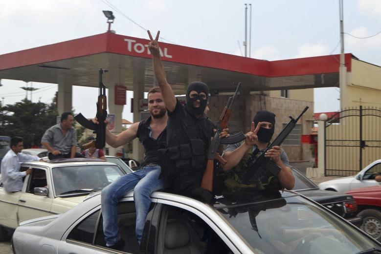 Unidentified gunmen celebrate during the arrival of Lebanese Army soldier Ibrahim Moustafa Shaaban, who was captured by Islamist militants in Arsal, upon his arrival in Al-Mohamara village after his release, in Akkar August 31, 2014. Islamist Nusra Front, a group linked to al Qaeda, on Saturday released four Sunni soldiers and a Sunni policeman whom they captured earlier this month, including Shaaban, a source close to the group said. The circumstances of their release were not immediately clear. REUTERS/Stringer