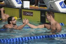 Jun 20, 2014; Santa Clara, CA, USA; Michael Phelps (USA), left, shakes hands with Nathan Adrian (USA), right, after the men's 100-meter freestyle finals of the Arena Grand Prix at George F. Haines International Aquatic Center. Kyle Terada-USA TODAY Sports