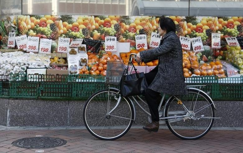 A woman rides a bicycle past outside a food store in Tokyo February 17, 2014.  REUTERS/Yuya Shino
