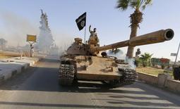 Боевики Исламского государства на танке во время парада в провинции Ракка в Ираке 30 июня 2014 года. Президент США Барак Обама выступит перед американцами и проконсультируется с законодателями на этой неделе, чтобы представить план действий против боевиков Исламского государства. REUTERS/Stringer