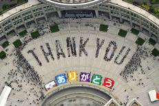"An aerial view shows people sitting in formation to the words ""thank you"" and displaying signs that collectively read ""Arigato"" (Thank You) during an event celebrating Tokyo being chosen to host the 2020 Olympic Games, at Tokyo Metropolitan Government Building in Tokyo, in this file photo taken by Kyodo September 8, 2013. REUTERS/Kyodo/File"