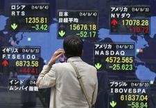 Un hombre mira una pantalla que muestra el índice Nikkei y los valores de otros  países en Tokio. Imagen de archivo, 4 septiembre, 2014.  El dólar se apreciaba frente a una serie de divisas el martes, lo que impulsaba a las acciones de los exportadores japoneses pero empujaba a la baja al petróleo, el oro y los papeles de las firmas energéticas. REUTERS/Issei Kato