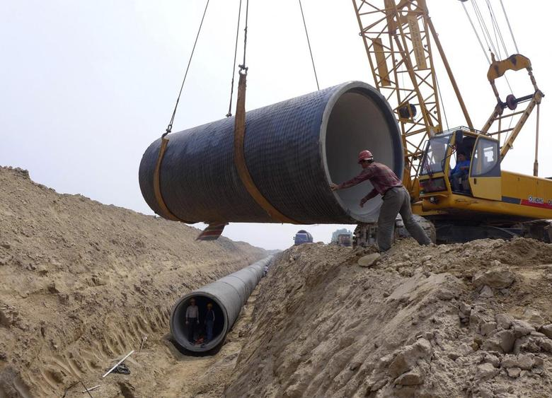 Workers install a pipeline at a construction site as part of China's South-North Water Diversion Project, which aims to relieve the country's drought-ridden north by diverting water from the southern and central part of the country, in Cangzhou, Hebei province, May 4, 2014. Picture taken May 4, 2014. REUTERS/China Daily