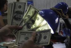 Imagen de archivo de un empleado cambiando dólares en una casa de cambios en Manila, sep 19 2013. El dólar retrocedía el jueves desde su máximo en seis años contra el yen tras unos datos que mostraron que creció el número de estadounidenses que solicitaron por primera vez el seguro por desocupación la semana pasada. REUTERS/Romeo Ranoco