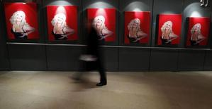 A man walks past posters put up at the Royal Opera House on the opening night of the opera based on the life of Anna Nicole Smith, in central London, February 17, 2011. REUTERS/Andrew Winning