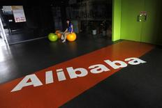 An employee sits next to a logo of Alibaba during a media tour organised by government officials at the company's headquarters on the outskirts of Hangzhou, Zhejiang province, June 20, 2012.   REUTERS/Carlos Barria