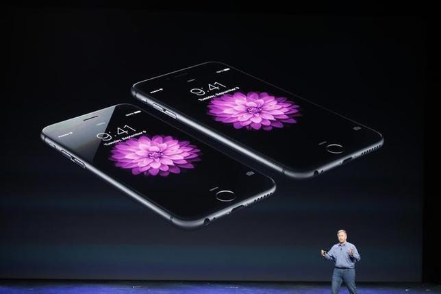 Phil Schiller, Senior Vice President at Apple Inc., speaks about the iPhone 6 (foreground) and the iPhone 6 Plus during an Apple event at the Flint Center in Cupertino, California, September 9, 2014. REUTERS/Stephen Lam