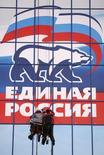 """Рабочие крепят постер """"Единой России"""" в Ставрополе 15 ноября 2007 года. Кандидаты Кремля одержали победу на всех региональных выборах, прошедших в России в воскресенье, и партия власти объяснила свой высокий результат рейтингом Владимира Путина, а ее критики - фальсификациями. REUTERS/Eduard Korniyenko"""
