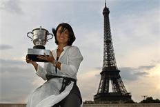 Li Na of China poses with her trophy near the Eiffel Tower in Paris after winning her women's final against Francesca Schiavone of Italy at the French Open tennis tournament at the Roland Garros stadium in Paris June 4, 2011.  REUTERS/Charles Platiau