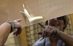 Женщина изучает витрину магазина Jimmy Choo в Риме 7 октября 2008 года. Британский люксовый обувной бренд Jimmy Choo объявил о намерении провести IPO в Лондоне, при этом его владелец - JAB Luxury - частично выйдет из капитала, а сама компания может быть оценена как минимум в 700 миллионов фунтов ($1,2 миллиарда). REUTERS/Tony Gentile