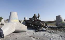 Украинские военные осматривают подбитый танк у Мариуполя 6 сентября 2014 года. Мохамед Эль-Эриан, главный экономический консультант в Allianz SE, предупредил, что мировые рынки не полностью оценивают риск, представляемый украинским кризисом, который может ввергнуть Европу в рецессию. REUTERS/Vasily Fedosenko