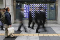 Un hombre mira una pizarra electrónica con índices económicos en Tokio. Imagen de archivo, 04 diciembre, 2013. Las bolsas de Asia caían el jueves, borrando ganancias iniciales luego de que se desvaneció el entusiasmo por un rebote en Wall Street. El índice MSCI de acciones asiáticas fuera de Japón retrocedía un 0,4 por ciento después de tocar un mínimo en cuatro meses. REUTERS/Toru Hanai