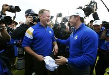 Team Europe golfer Jamie Donaldson (L) celebrates with teammate Rory McIlroy after winning his match against U.S. player Keegan Bradley to retain the Ryder Cup for Europe on the 15th green during the 40th Ryder Cup at Gleneagles in Scotland September 28, 2014.   REUTERS/Eddie Keogh