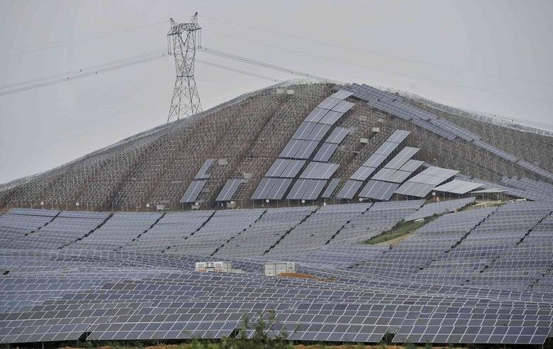 An electricity pylon is seen above a solar power plant which is under construction on a hill in Wuhu, Anhui province, September 16, 2014. REUTERS/Stringer