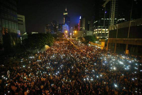 Manifestantes segurar seus celulares como eles bloquear a rua principal do distrito financeiro central, em frente à sede do governo, em Hong Kong 29 de setembro de 2014 REUTERS / Carlos Barria