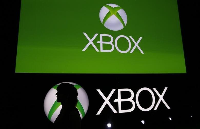 A Spanish Games blogger is silhouetted against the logo of Microsoft's Xbox during the Xbox Play Day 2014, before the Gamescom 2014 fair in Cologne August 12, 2014. REUTERS/Wolfgang Rattay