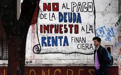 Un hombre camina junto a un graffiti en una calle de Buenos Aires alusivo a la crisis de deuda en Argentina, jul 31 2014. La recaudación de impuestos de Argentina subió un 37,5 por ciento en septiembre en la comparación interanual al totalizar 98.719 millones de pesos (11.714 millones de dólares), dijo el miércoles el Gobierno, en un dato que se ubicó por encima de lo esperado por el mercado.  REUTERS/Marcos Brindicci