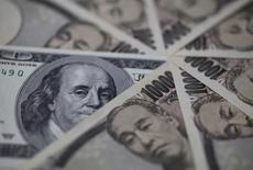 Купюры валют доллар США и иена в Токио 28 февраля 2013 года. Курс иены растет, так как инвесторы не хотят рисковать после выхода слабых производственных показателей многих регионов мира. REUTERS/Shohei Miyano