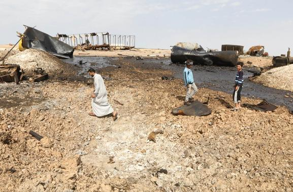 Locals inspect damage at an oil refinery that was targeted by what activists said were U.S.-led air strikes at al-Khaboura village, near the Syrian town of Tel Abyad of Raqqa governate, October 2, 2014. REUTERS/Stringer