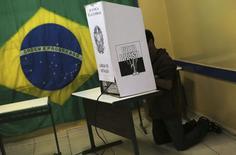 Homem se ajoelha na cabine de votação durante eleição para presidente em São Bernardo do Campo.  REUTERS/Nacho Doce