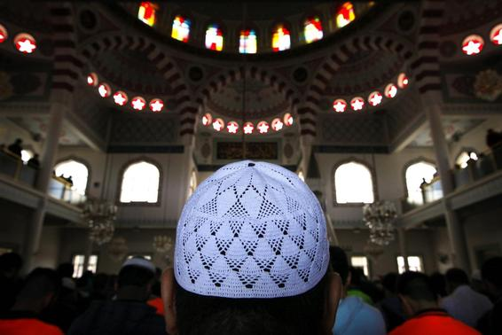 A man wearing an Islamic prayer cap, or 'Kufi', prays with other Muslim worshippers in the Gallipoli Mosque located in the western Sydney suburb of Auburn September 26, 2014. REUTERS-David Gray