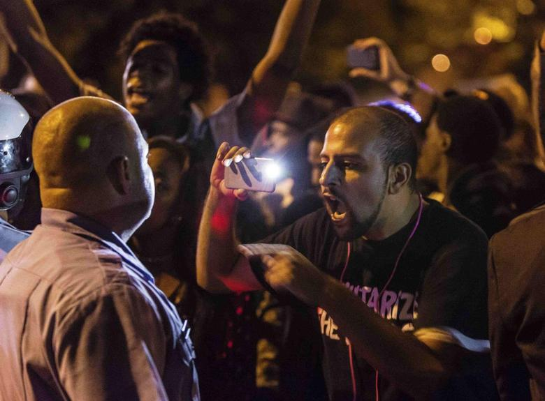 Demonstrator Bassem Masri confronts a St. Louis police officer following an incident in which a white off-duty policeman shot and killed a black teenager in St. Louis, October 8, 2014.  REUTERS/Kenny Bahr