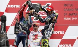 Yamaha MotoGP rider Valentino Rossi (R) of Italy and Yamaha MotoGP rider Jorge Lorenzo (L) of Spain pour champagne on Honda MotoGP rider Marc Marquez (C) of Spain after the Japanese Grand Prix at the Twin Ring Motegi circuit in Motegi, north of Tokyo October 12, 2014. REUTERS/Toru Hanai