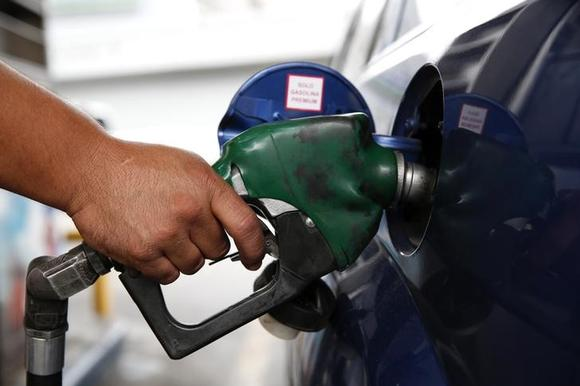 An employee pumps gas into a car at a gas station of the state oil company PDVSA in Caracas December 16, 2013. REUTERS/Carlos Garcia Rawlins
