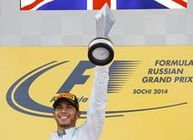 Mercedes Formula One driver Lewis Hamilton of Britain celebrates with the trophy after winning the first Russian Grand Prix in Sochi October 12, 2014. REUTERS/Laszlo Balogh