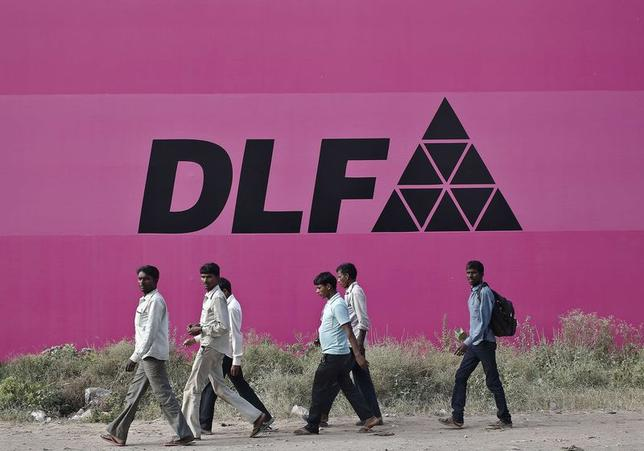 Workers walk past a billboard of DLF Ltd. at Gurgaon on the outskirts of New Delhi October 14, 2014. REUTERS/Anindito Mukherjee
