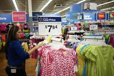 An employee cleans a clothes rack at the Walmart Supercenter in Bentonville, Arkansas June 5, 2014.   REUTERS/Rick Wilking