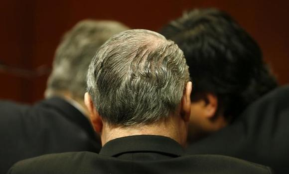 Irish priest John O'Reilly (C, back to camera) of the Legionaries of Christ conservative Roman Catholic order and his two lawyers (L and R) attend his hearing at a court in Santiago August 27, 2013. REUTERS/Ivan Alvarado/Files