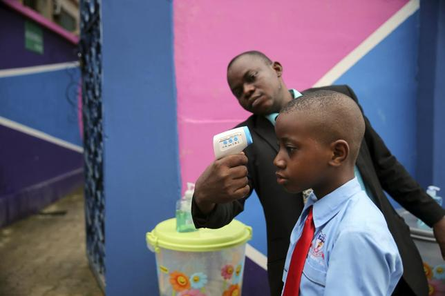 A school official takes a pupil's temperature using an infrared digital laser thermometer in front of the school premises, at the resumption of private schools, in Lagos in this September 22, 2014 file photo. REUTERS/Akintunde Akinleye/Files