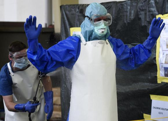 A volunteer of the German army Bundeswehr, wearing a protective suit, is disinfected by a colleague during an Ebola training session at the Marseille barracks in Appen, October 23, 2014. REUTERS/Fabian Bimmer