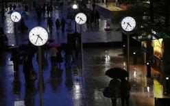 Personas caminan en el distrito financiero de Canary Wharf en Londres. Imagen de archivo, 11 noviembre, 2013. El sólido crecimiento económico británico se debilitó como estaba previsto en el tercer trimestre, en momentos en que el sector de servicios ralentizó su expansión y la industria creció a su menor ritmo en 18 meses, según datos oficiales publicados el viernes. REUTERS/Eddie Keogh