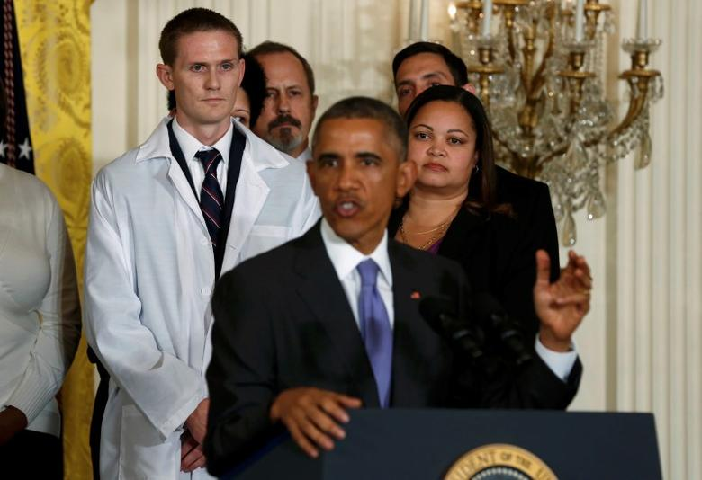 Healthcare professionals listen as U.S. President Barack Obama (C) speaks about the government's Ebola response from the East Room of the White House in Washington, October 29, 2014. REUTERS/Larry Downing