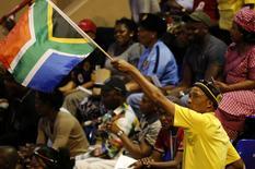 Homem ergue bandeira da África do Sul em cerimônia de homenagem a Senzo Meyiwa e outros esportistas sul-africanos mortos recentemente. 30/10/2014 REUTERS/Siphiwe Sibeko