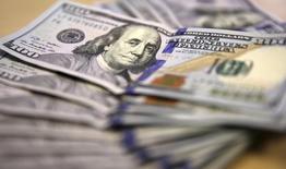 Долларовые купюры в Йоханнесбурге 13 августа 2014 года. Доллар возобновил рост после фиксации прибыли, вернувшись к многолетним максимумам. REUTERS/Siphiwe Sibeko