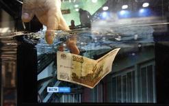 Сотрудник компании 3M опускает 100-рублевую купюру в емкость с противопожарной жидкостью на выставке в Санкт-Петербурге 15 ноября 2011 года. Банк России ограничил валютные интервенции, вплотную приблизившись к свободному плаванию курса рубля, но не стал сразу отменять валютный коридор, чтобы избежать шока на рынке, где основным инструментом до конца года должны стать операции валютного репо, сказала первый зампред ЦБР Ксения Юдаева. REUTERS/Alexander Demianchuk