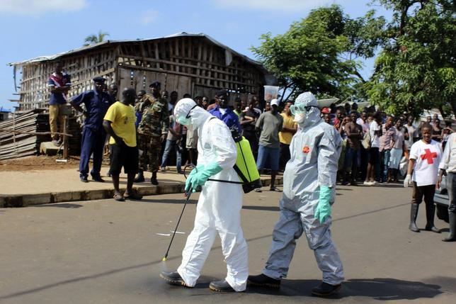 Health workers spray themselves with chlorine disinfectants after removing the body a woman who died of Ebola virus in the Aberdeen district of Freetown, Sierra Leone, October 14, 2014. REUTERS/Josephus Olu-Mammah