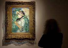 "A woman looks at ""Le Printemps"", Edouard Manet's 1881 portrait of the actress Jeanne Demarsy, during a media preview at Christie's auction house in New York, October 31, 2014. REUTERS/Brendan McDermid"