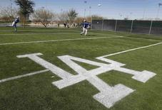 Los Angeles Dodgers players warm up on a side field as they prepare for their bullpen session during MLB Cactus League spring training at the team's facility in Glendale, Arizona in this February 14, 2013 file photo. REUTERS/Ralph D. Freso/Files