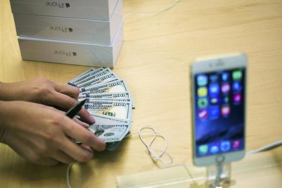 An employee counts money while selling new iPhone 6 phones at the Fifth Avenue Apple store on the first day of sales in Manhattan, New York September 19, 2014.   REUTERS-Adrees Latif