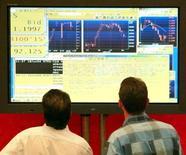Трейдеры у экрана с графиками фондовых котировок на ММВБ 18 июня 2004 года. Российские фондовые индексы вращаются в среду вокруг сложившихся значений на фоне скромных колебаний рубля, а РДР Русала резко выросли после квартального отчета. REUTERS/Sergei Karpukhin