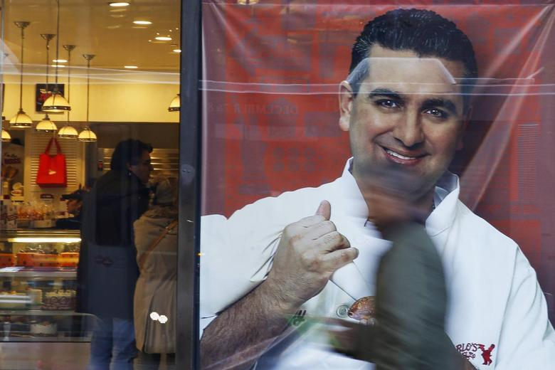 People walk by a photo of celebrity chef Buddy Valastro outside his 'Cake Boss' cafe in New York November 13, 2014. REUTERS/Shannon Stapleton