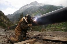 Сварщик скрепляет трубы газопровода у поселка Бурон в Северной Осетии 17 июня 2009 года. Объявивший допэмиссию крупнейший производитель стальных труб в РФ - Трубная металлургическая компания - рассчитывает продать госкорпорации Роснано пакет в 6 процентов в течение нескольких недель, сказал в интервью Рейтер замгендиректора компании. REUTERS/Eduard Korniyenko