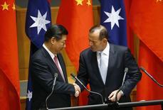 Le président chinois Xi Jinping et le Premier ministre australien Tony Abbott au Parlement, à Canberra. La Chine et l'Australie ont signé lundi un accord préliminaire à un traité de libre-échange en négociations depuis plus de dix ans susceptible d'ouvrir les marchés chinois aux entreprises australiennes et de lever les restrictions pesant sur les investissements chinois. /Photo prise le 17 novembre 2014/REUTERS/David Gray