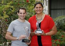 World-record pole vaulter Renaud Lavillenie of France (L) and shot putter Valerie Adams of New Zealand pose with their 2014 IAAF Athletes of the Year trophies in Monte Carlo November 21, 2014.   REUTERS/Eric Gaillard